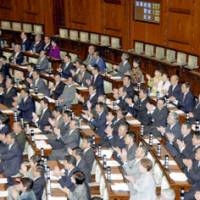Opposition Party lawmakers applaud after the opposition-sponsored bill on the use of pension premiums was passed Friday in the House of Councilors in a vote of 132-95. | KYODO PHOTO