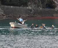 Antiwhaling activists are prodded with a pole by fishermen as they conduct a ceremony in the water Monday to honor the spirits of cetaceans slaughtered here. | PHOTO COURTESY OF SURFERS FOR CETACEANS