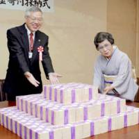 Chizuko Yokomizo offers ¥1 billion Friday to Mayor Chosei Sawa Minamiashigara, Kanagawa Prefecture, at City Hall. | KYODO PHOTO