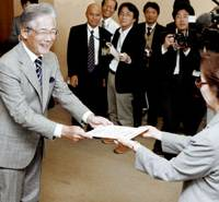 Kunio Hiramatsu, elected mayor of Osaka on Sunday, receives a certificate of victory from a member of the election administration commission at City Hall on Monday. | KYODO PHOTO