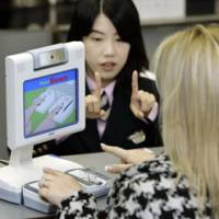 An immigration official shows a traveler how to use a digital fingerprint reader at Narita International Airport on Tuesday. | AP PHOTO