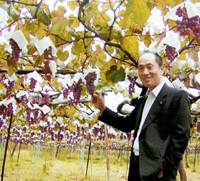 Yuji Aruga, president of Katsunuma Winery Co., stands in a vineyard in Koshu, Yamanashi Prefecture. | KYODO PHOTO