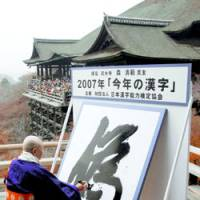 The Chinese character 'nise,' chosen as kanji of the year, is unveiled Wednesday at Kiyomizu Temple in Kyoto by chief priest Seihan Mori. Nise means 'fake.' | KYODO PHOTO