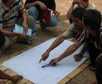 Members of Japan Volunteer Center work on a map of a forest that will be jointly owned by rural Laotians. | PHOTO COURTESY OF JAPAN VOLUNTEER CENTER