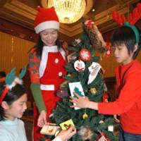 Asuka Uozumi, 12, her brother, Kenta, 9, and their mother, Keiko, trim a Christmas tree during a decoration contest last December at Sheraton Grand Tokyo Bay. | SATOKO KAWASAKI PHOTO