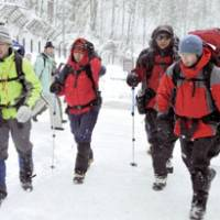 Survivors of Monday's avalanche on Mount Yarigatake (from right) Yutaka Takeuchi, Motoo Suzuki and Miyoko Nagase descend Wednesday morning to a base in Takayama, Gifu Prefecture. | KYODO PHOTO