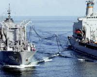 The Maritime Self-Defense Force refueling ship Tokiwa (left) supplies fuel to a U.S. naval vessel in the Arabian Sea in February 2003. | KYODO PHOTO