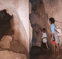 Local residents peer into a cave used by Japanese straggler Hiroo Onoda as a hideout. The cave is called 'puting bato,' which means 'white stone' in English. | PHOTO COURTESY OF A LOCAL RESIDENT / KYODO