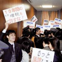 Lawmakers from the Democratic Party of Japan block the entrance to a Diet committee room Wednesday, holding signs opposing decades of extra auto-related taxes. | KYODO PHOTO
