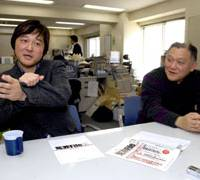 Masaru Takasaki, publisher of the new magazine Enzai File focusing on fishy criminal cases, explains how a man on a train was mistaken as a groper, as writer Kyohei Imai looks on at their office in Shinjuku Ward, Tokyo. | YOSHIAKI MIURA PHOTO