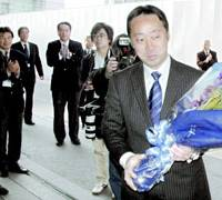 Yoshihiko Fukuda receives a bouquet from city employees Tuesday as he arrives at Iwakuni City Hall to begin his first day as mayor. | KYODO PHOTO