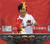 The end: Athens Olympics marathon gold-medalist Mizuki Noguchi lights a caldron to signal the end of the Japanese leg of the Olympic torch relay in Nagano on Saturday. | AP PHOTO