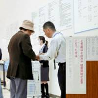 Nitty-gritty: An official at a hospital in the city of Tokushima tells a senior patient about the new health insurance system for people aged 75 or older on April 4. | KYODO PHOTO