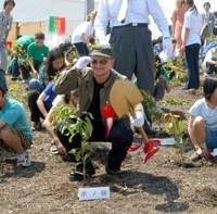 Getting dirty: U2 band leader Bono plants a tree with children Tuesday during an event on a man-made island in Tokyo Bay. The Umi-no-Mori event was part of the Tokyo Metropolitan Government's Green Island project. | YOSHIAKI MIURA PHOTO