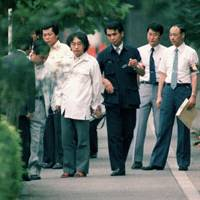 Modus operandi: Tsutomu Miyazaki is surrounded by investigators on a street in Koto Ward, Tokyo, in August 1989 as they try to piece together how he kidnapped one of his victims. | KYODO PHOTO