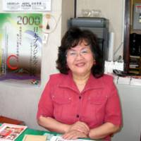 Community-builder: Shoko Takano, who runs the Oizumi Nippaku Center in the Japanese-Brazilian community in Oizumi, Gunma Prefecture, is interviewed recently in her office. In her younger days, Takano poses with her younger sister and friends from a high school in Santa Catarina, Brazil. | AKEMI NAKAMURA PHOTO, COURTESY OF SHOKO TAKANO PHOTO