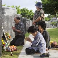 Guns long silent: Relatives of people who died during the Battle of Okinawa 63 years ago offer prayers to the dead Monday at a memorial park in Itoman, Okinawa Prefecture. | KYODO PHOTO
