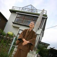 War trophy: Kokichi Nishimura stands in front of his house in Kazo, Saitama Prefecture. Protruding from his garden wall is a B-24 bomber's propeller that he had shipped back from Papua New Guinea. | DAVID MCNEILL