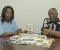 Proof of hardship: Zambian farmer Joyce Mwanje (left) and Joseph Ssuuna, representative of a nongovernmental organization, show pictures of how African peasant farmers work during an interview in Tokyo on Tuesday. | KYODO PHOTO