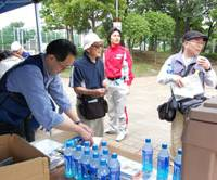Refreshments?: A man serves soft drinks to disaster drill participants last month at Shinkoiwa Park in Tokyo's Edogawa Ward, one of the prefecture's several designated evacuation sites. | KAZUAKI NAGATA PHOTO