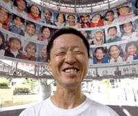 Let it be your umbrella: Art director and photographer Koji Mizutani is all smiles Friday under some 100 photos he took of grinning Asian youths, at Metro Hat in the Roppongi Hills complex in Minato Ward, Tokyo. Some 1,500 of his photos were displayed in the opening ceremony of the Olympics at the Beijing National Stadium. | YOSHIAKI MIURA PHOTO