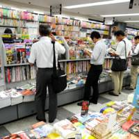 Browsing the shelves: Customers check out magazines at the Toranomon Shobo bookstore in Minato Ward, Tokyo, last week. | SATOKO KAWASAKI PHOTO