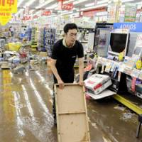 A Yamada Denki Co. employee tries to remove water from a flooded shop floor Friday at an outlet in Okazaki, Aichi Prefecture, after heavy rain struck the area overnight. The consumer electronics retail giant has yet to assess the damage. | KYODO PHOTO