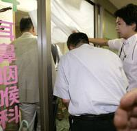 Loud and clear: Hokkaido police raid the Sapporo clinic of Yoshiaki Maeda on Wednesday. The doctor is suspected of providing false diagnoses so that his patients could illegally obtain physical disability certificates. | KYODO PHOTO