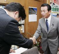 Stumping for votes: Liberal Democratic Party Secretary General Taro Aso seeks the support of a fellow LDP lawmaker in the party's presidential election at a Diet office building Thursday. | KYODO PHOTO