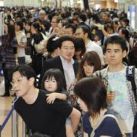 Jam-packed: Passengers wait for their flights at Haneda airport in Tokyo on Sunday morning. | KYODO PHOTO