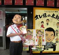 Another Aso: Toshio Okubo, president of Daito Co., which sells sweets that portray politicians, wears a Taro Aso mask in front of his shop Monday in Tokyo's Akihabara district. | NATSUKO FUKUE PHOTO