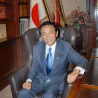 Seat at the top table: Taro Aso sits at the Liberal Democratic Party president's desk in the LDP headquarters in Tokyo on Monday. | YOSHIAKI MIURA PHOTO