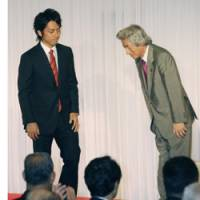 From father to son: Former Prime Minister Junichiro Koizumi bows to his son Shinjiro during a meeting in Yokosuka, Kanagawa Prefecture, on Saturday. | KYODO PHOTO