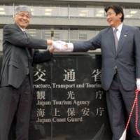 Good luck: Yoshiaki Honpo (left), commissioner of the Japan Tourism Agency, greets transport minister Kazuyoshi Kaneko on Wednesday during the agency's inauguration ceremony. | YOSHIAKI MIURA PHOTO