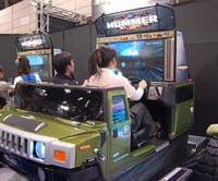 Dream machine: Visitors to the Amusement Machine Show in Makuhari Messe in Chiba Prefecture try out the 'Hummer' ride game at the Sega Corp. booth on Sept. 20. | KAZUAKI NAGATA PHOTO