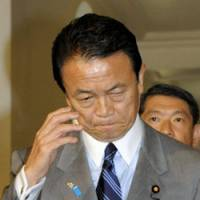 Not yet: Prime Minister Taro Aso walks through the Diet on Tuesday as word spread that no snap election will be held this year. | KYODO PHOTO