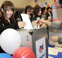 Democracy in action: A Japanese college student casts a ballot in a mock election for non-U.S. citizens Wednesday at the U.S. Embassy in Tokyo. | SATOKO KAWSAKI PHOTO