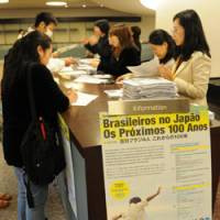 School daze: A poster for the symposium 'Brazilians in Japan: The next 100 years' adorns the reception counter at the event Sunday in Minato Ward, Tokyo. | SATOKO KAWASAKI PHOTO