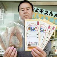 Season's greetings: An employee of a fishery cooperative of Susami, Wakayama Prefecture, shows off dried squid that can be used as New Year's postcards. | KYODO PHOTO