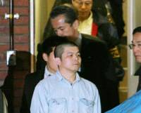 Suspect: Takeshi Koizumi, suspected of involvement in the murder of a former top bureaucrat and his wife, is taken from Kojimachi Police Station in Tokyo early Sunday. | KYODO PHOTO