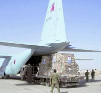 Offloading: An Air Self-Defense Force C-130H disgorges its cargo after arriving at Talil Airport in southern Iraq in March 2004. | KYODO PHOTO