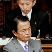 Looking for answers: Prime Minister Taro Aso listens to questions from lawmakers during a Diet session Nov. 18. | KYODO PHOTO