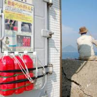Waiting for a bite: A fisherman waits beside the Takamatsu Coast Guard Office in Kagawa Prefecture, where a lifesaver made with used PET bottles is displayed. | KYODO PHOTO