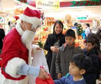 CEO Santa: Dressed in a Santa Claus costume, Sega Toys President and CEO Isao Kokubun hands out presents at Matsuzakaya department store in Tokyo's Ueno district Saturday during a Christmas event that involved other toy company executives. | KAZUAKI NAGATA