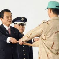 On duty: Prime Minister Taro Aso hands a certificate of gratitude to an Air Self-Defense Force officer last Wednesday at Komaki Air Base in Aichi Prefecture following the return of the final ASDF team from the mission in Iraq. The SDF may be asked to send troops to Afghanistan by the next U.S. administration. | KYODO PHOTO