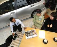 Dog eat dog: Sales manager Motoharu Ishii (left) talks with Chigusa Saito (right) and her husband, Shigeru, while petting their 3-year-old border collie Peach at a Honda dealership in Kawasaki on Nov. 24. | AP PHOTO