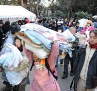 Breaking camp: Volunteers carry futon out of Hibiya Park in Tokyo on Monday, the final day of the tent village where they had been offering free food and shelter to laid-off temp workers. | SATOKO KAWASAKI PHOTO