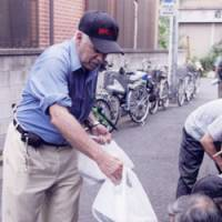 Dig in: Jean Le Beau of the NPO Sanyukai gives food to the homeless in Sanya, Tokyo, in 2008. | COURTESY OF SANYUKAI