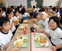 Chow down: Students at Shinonome Elementary School in Koto Ward, Tokyo, have lunch in their classroom in October 2006. | YOSHIAKI MIURA PHOTO