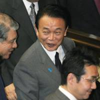 Mission accomplished: Prime Minister Taro Aso is elated Wednesday after a Lower House revote passes a bill to finance a second extra budget, including a 2 trillion yen cash handout program. | KYODO PHOTO